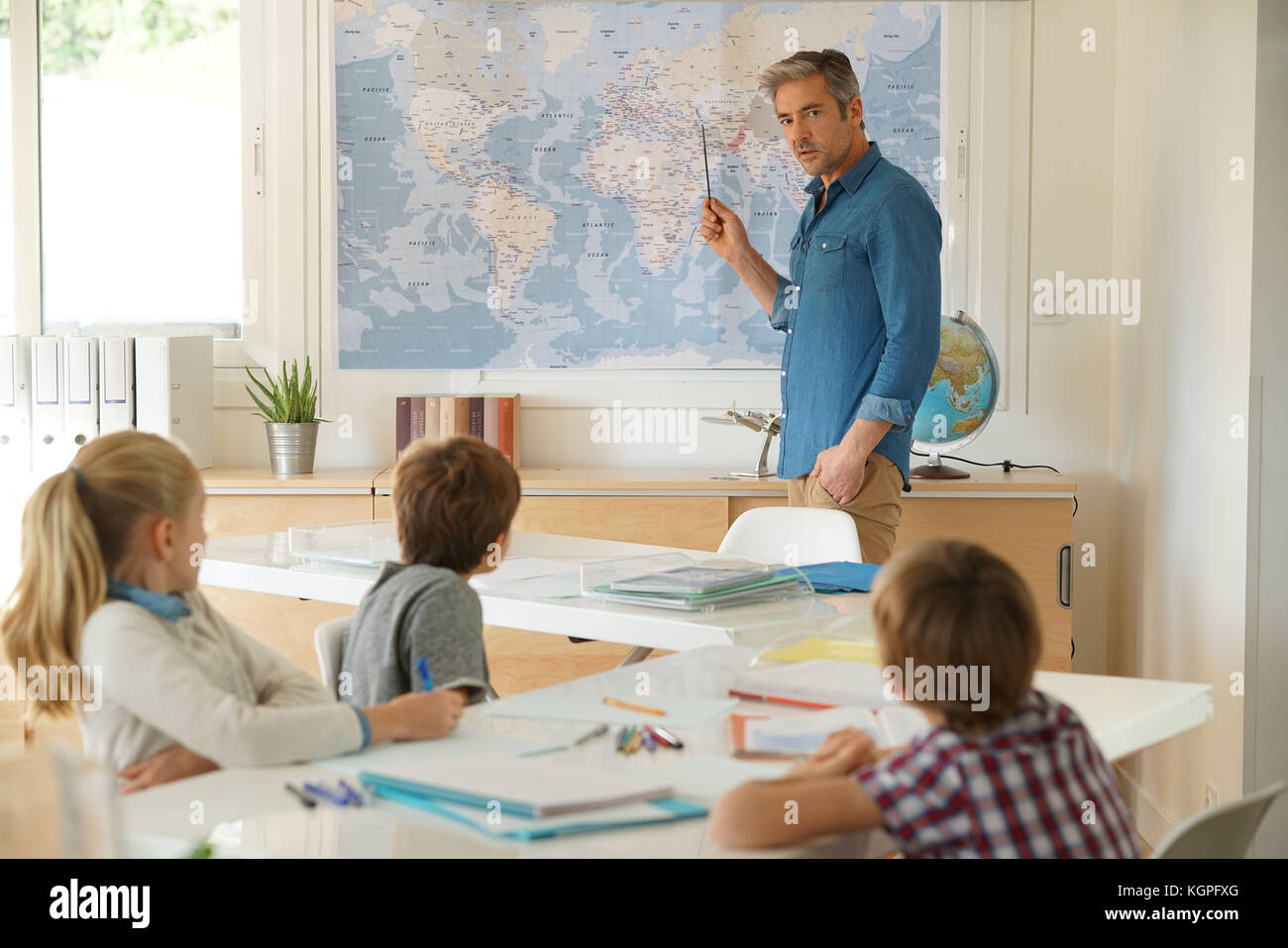 Teacher standing in classroom, kids attending geography lesson - Stock Image