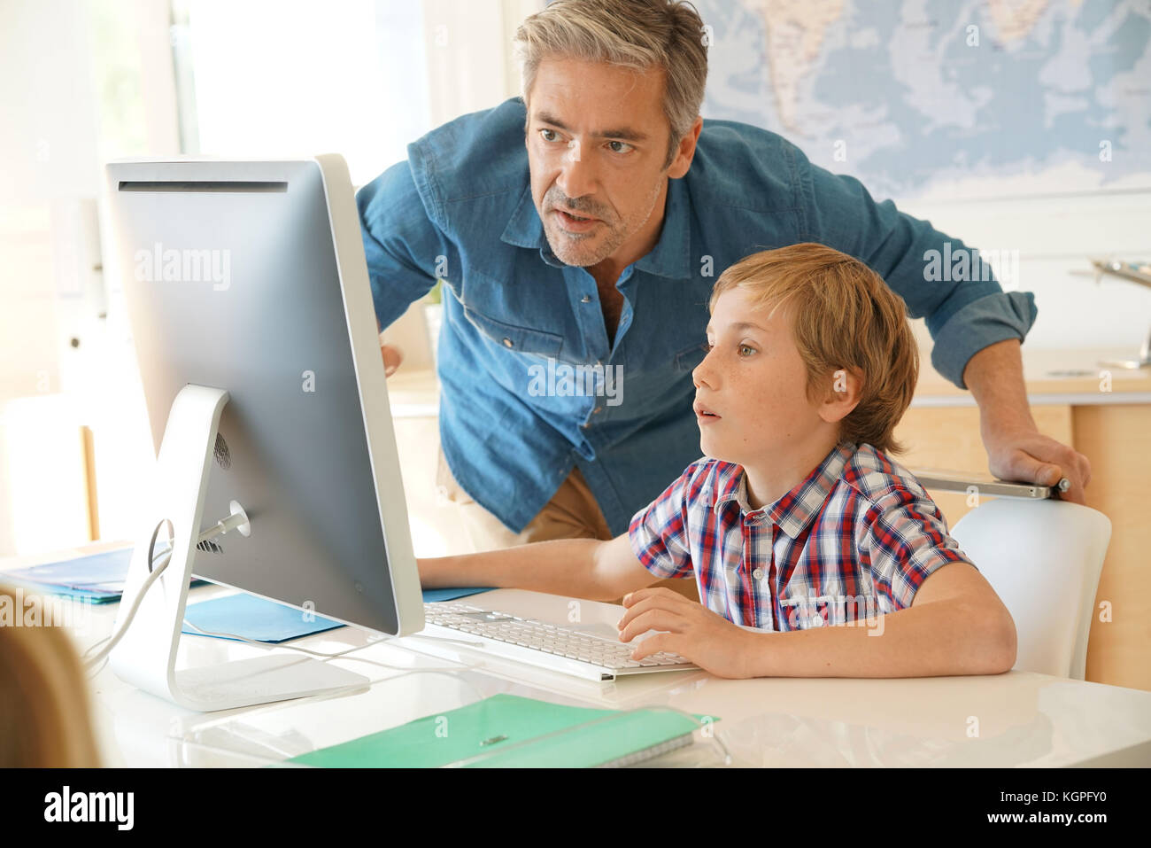 Schoolboy in computer lab with teacher helping - Stock Image
