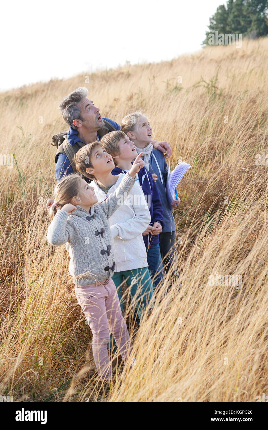 Teacher taking kids to countryside to explore nature - Stock Image