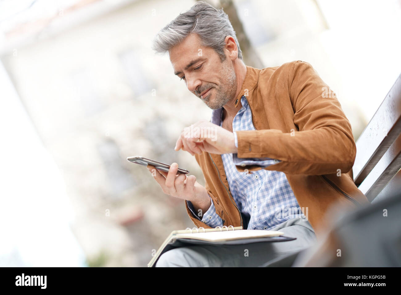 Businessman sitting on public bench, scheduling working day - Stock Image