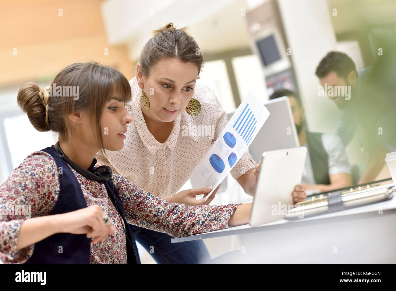 Young women in office working on digital tablet - Stock Image