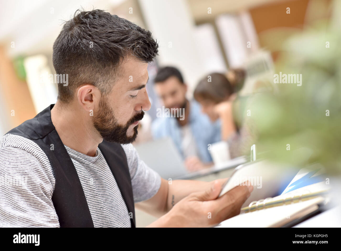 Trendy businessman in office working on tablet - Stock Image