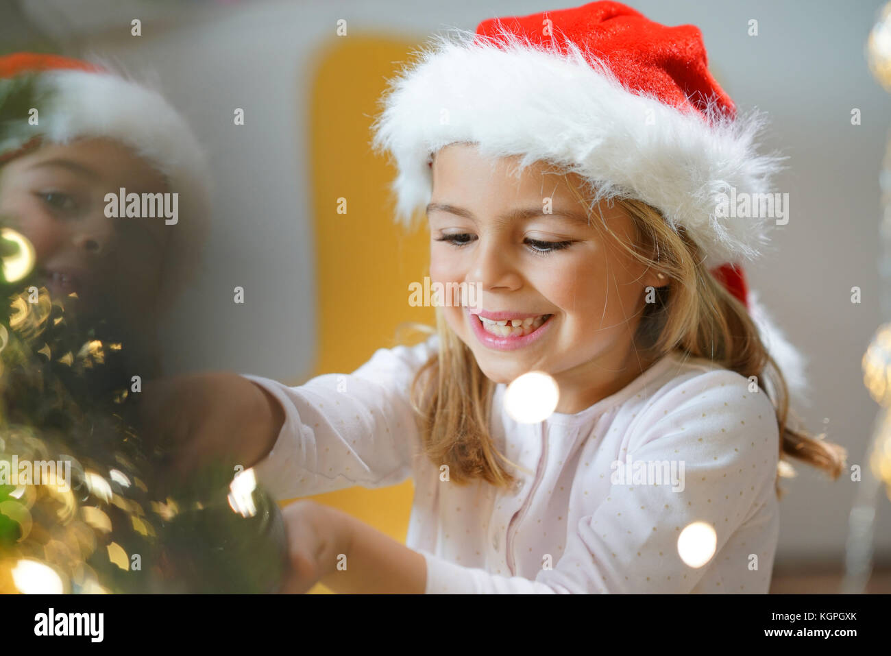 Portrait of cute little girl decorating Christmas tree - Stock Image