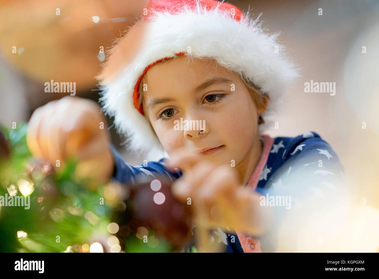 Portrait of cute little boy decorating Christmas tree - Stock Image