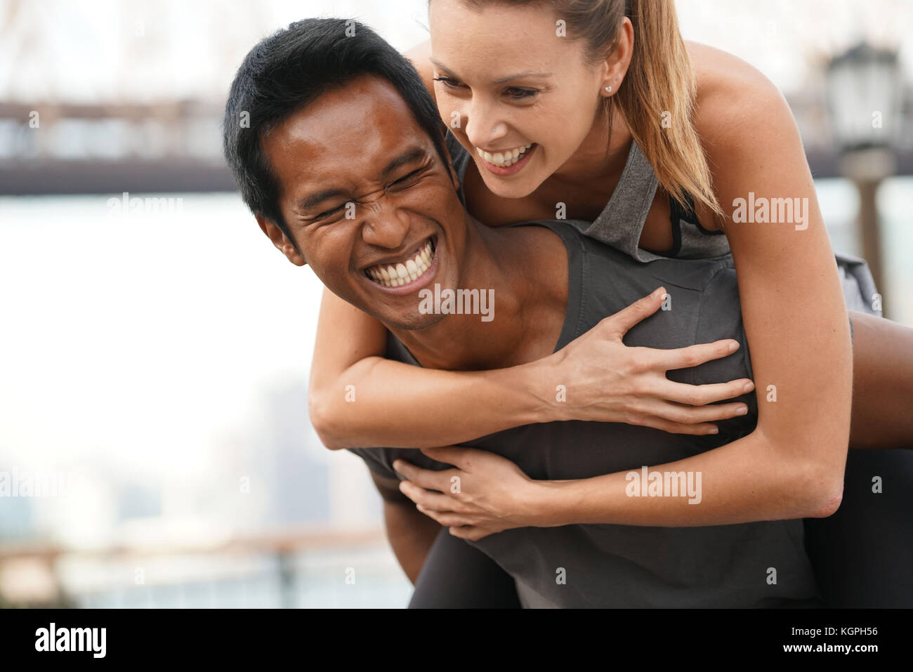 Man giving piggyback ride to girlfriend - Stock Image