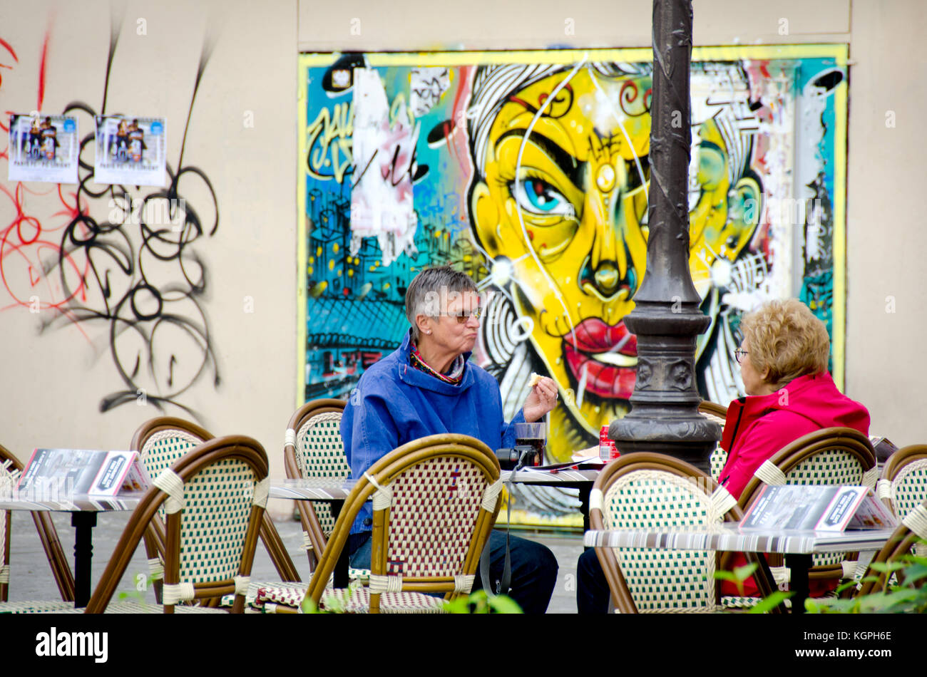 Paris, France. Two women sitting at a cafe table in Place Edmond Michelet with graffiti behind - Stock Image