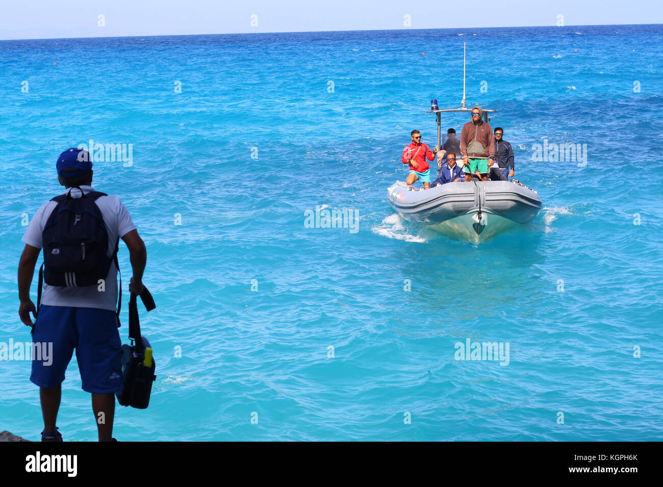 A man getting on board of a small inflatable Vigilanza boat on blue sea water in a Sardinian national park. - Stock Image