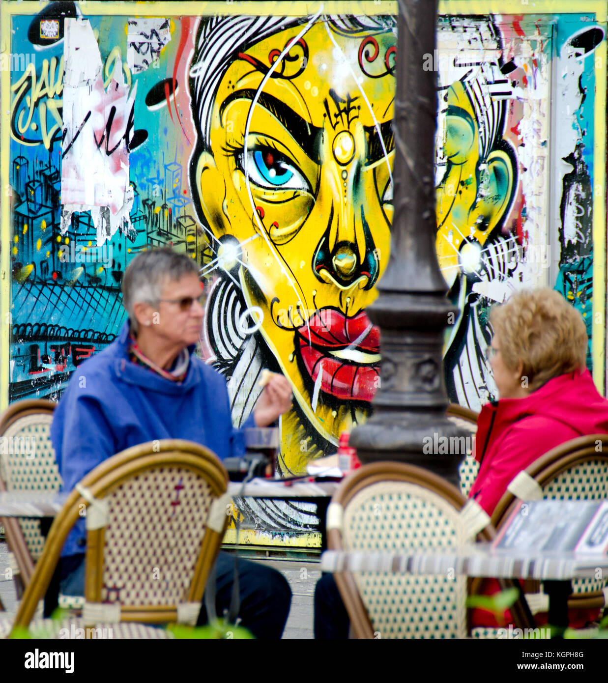 Paris, France. People sitting at a cafe table in Place Edmond Michelet with graffiti behind - Stock Image