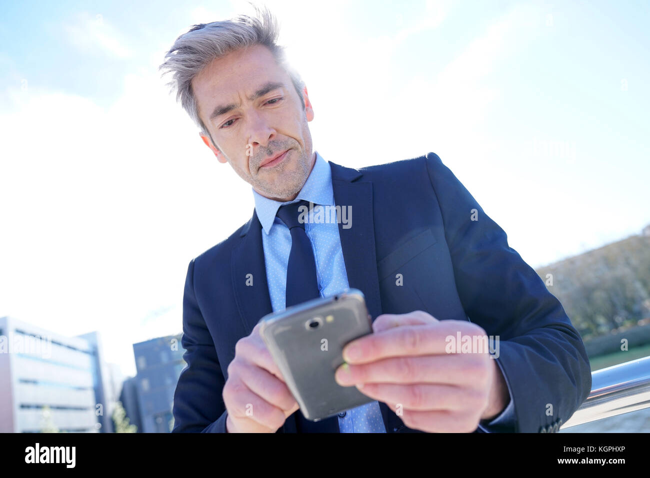Businessman using pda outside the office - Stock Image