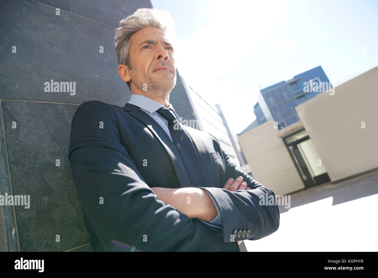 Portrait of businessman waiting outside building, leant on wall - Stock Image