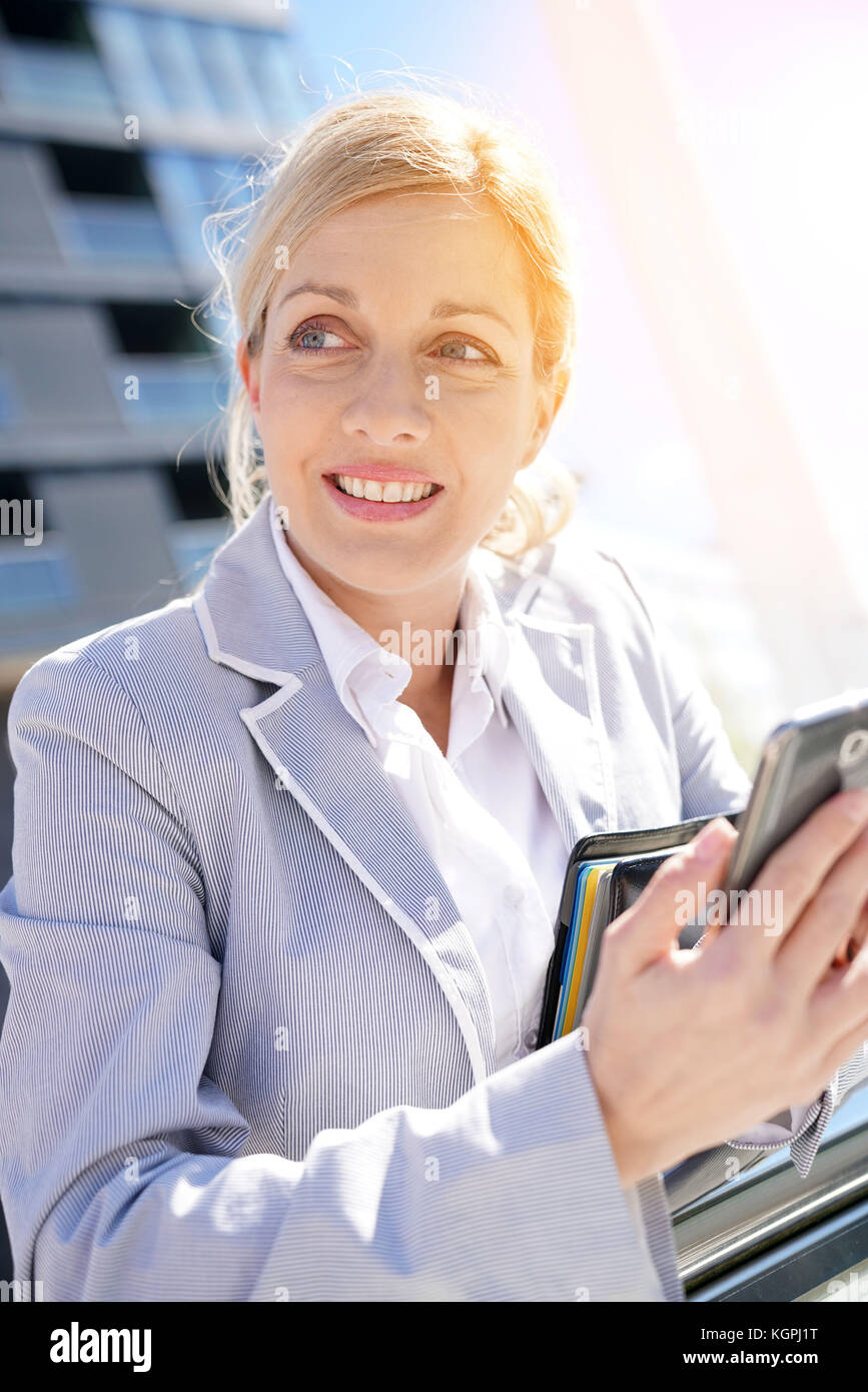 Businesswoman checking meeting schedule on smartphone - Stock Image