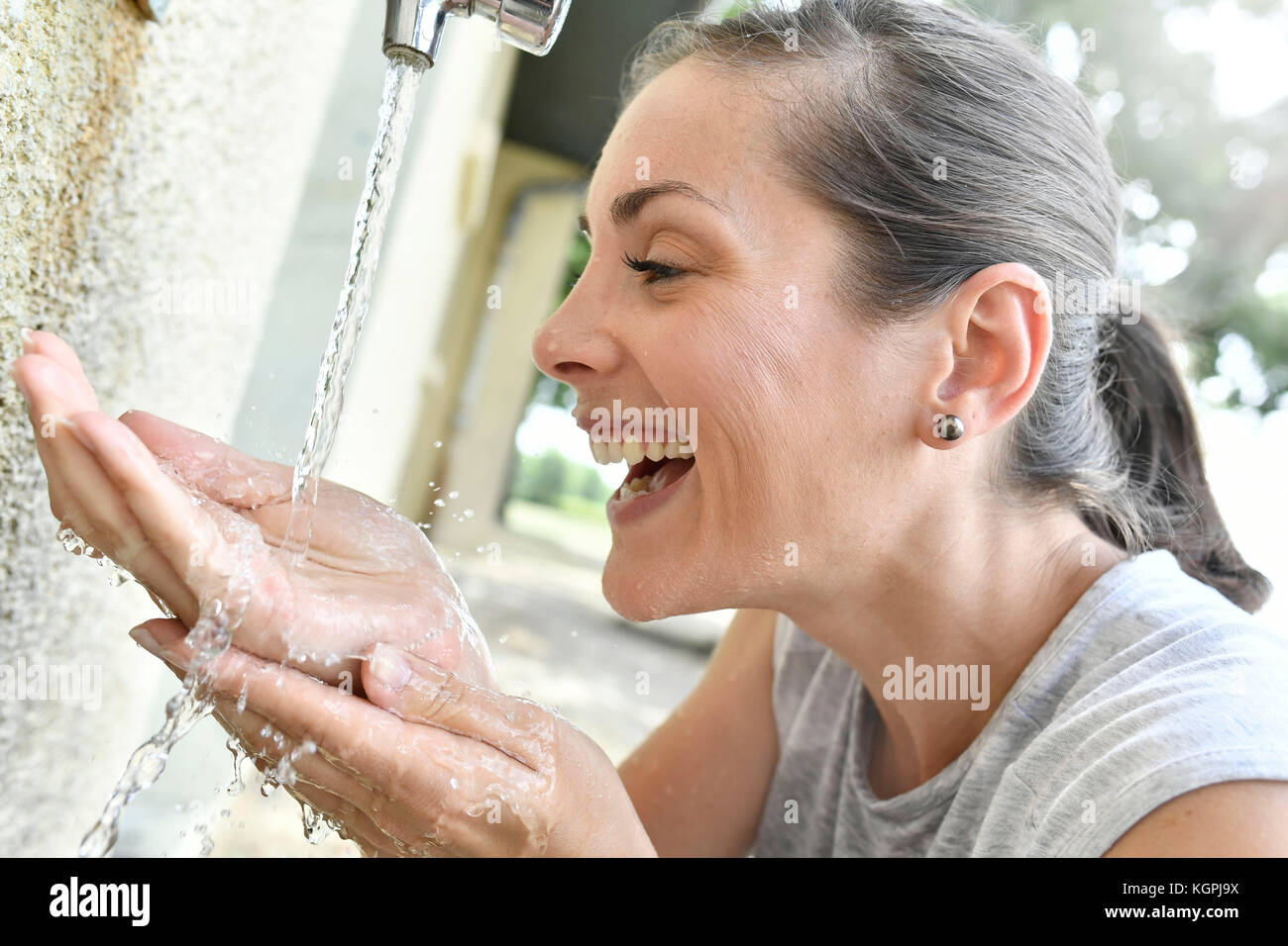 Portrait of cheerful girl drinking water from faucet - Stock Image