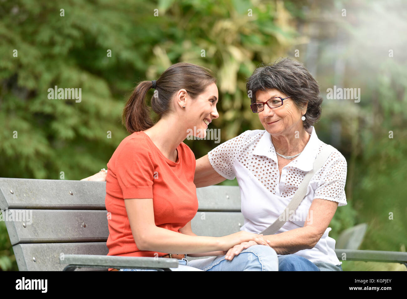 Senior woman with carer sitting on bench at the park - Stock Image