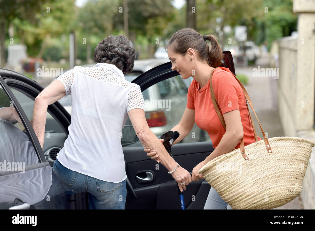 Young carer helping senior woman getting in car - Stock Image