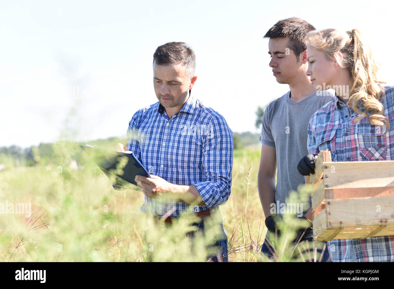 Young people with instructor in agricultural field - Stock Image
