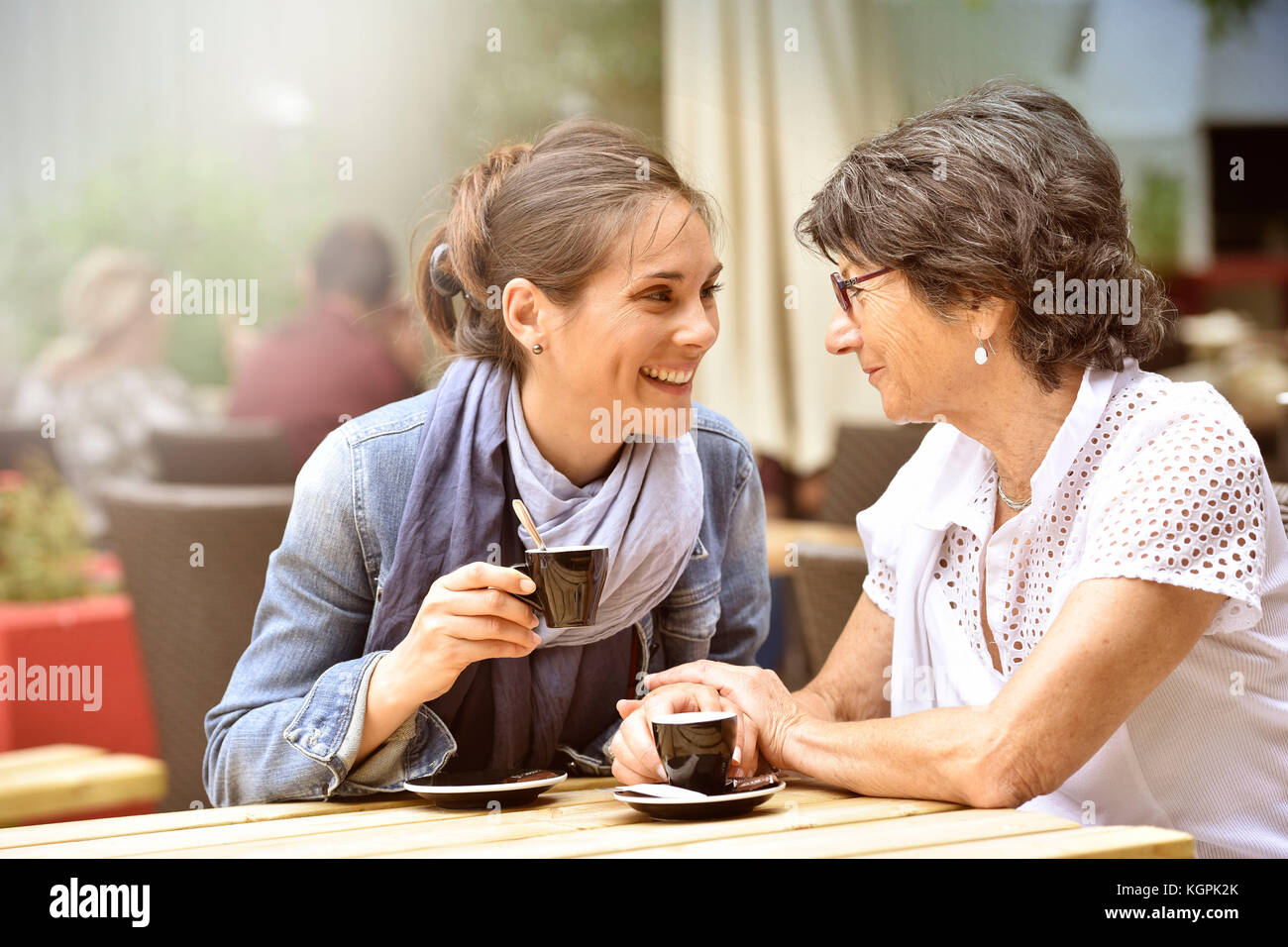 Senior woman with home carer having coffee together - Stock Image