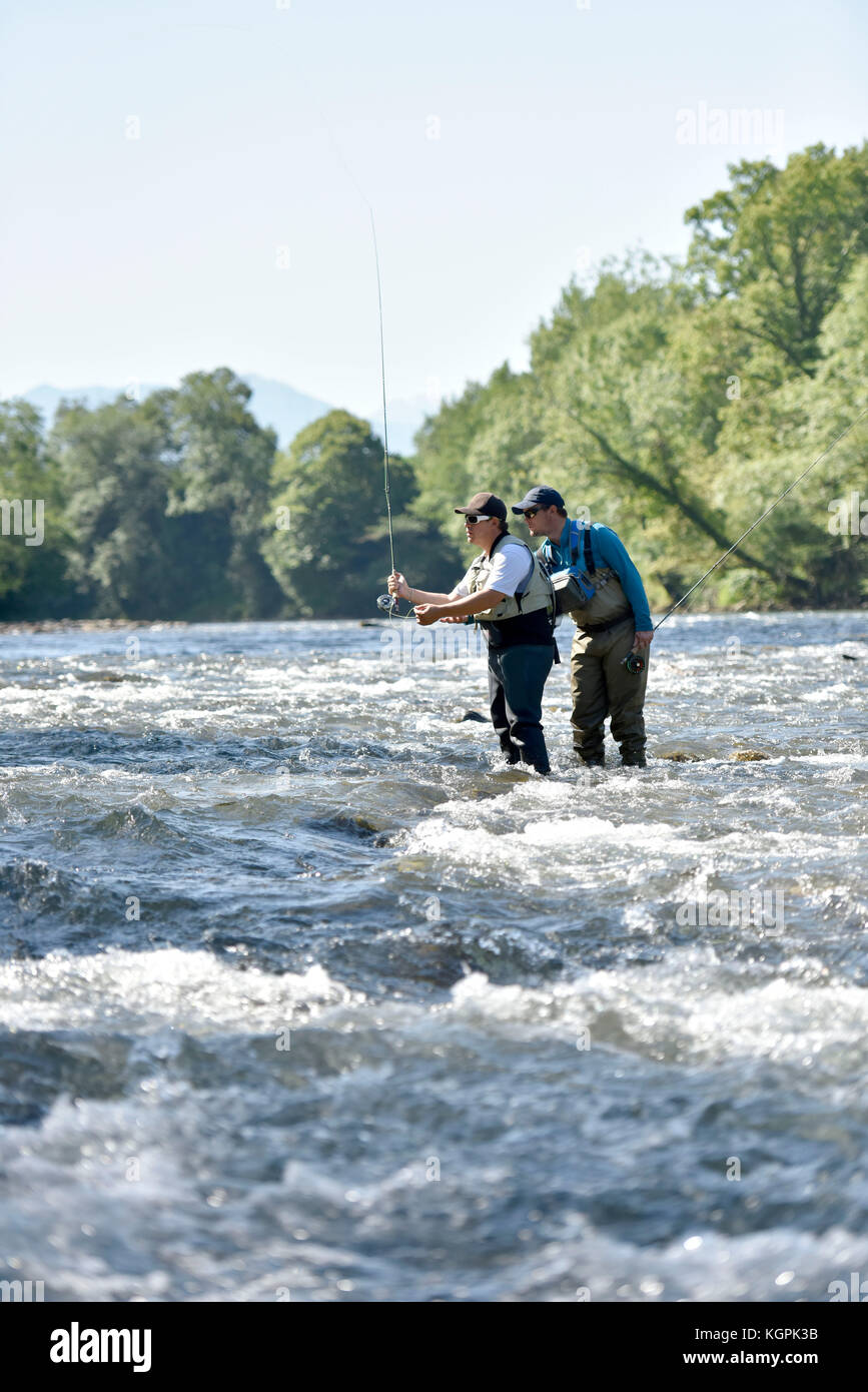 Flyfisherman with fishing guide in river - Stock Image