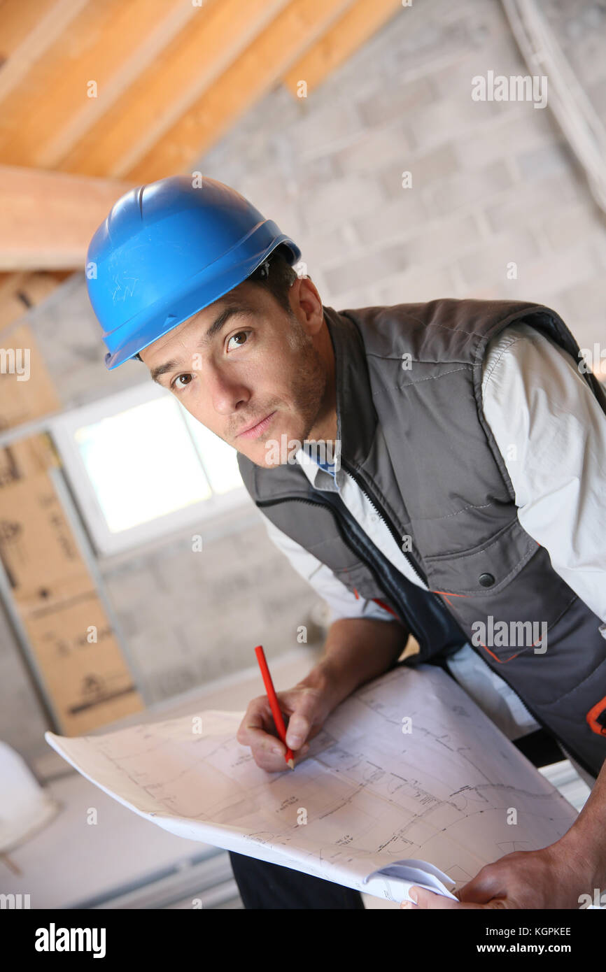 Construction manager on site reading blueprint Stock Photo