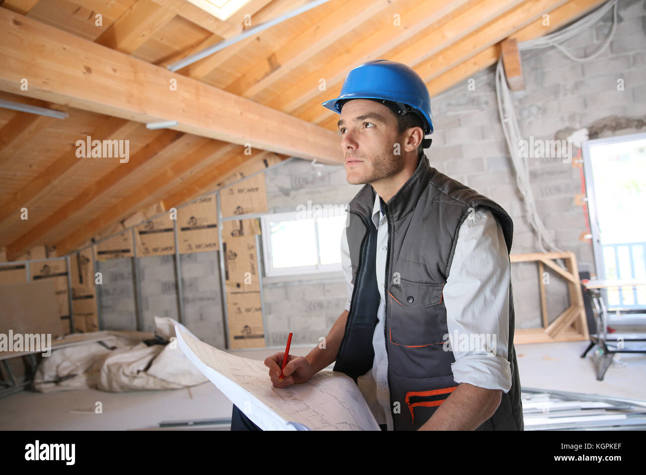 Construction manager on site reading blueprint - Stock Image