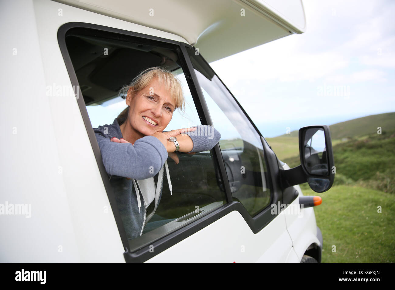 Happy senior woman by motorhome window - Stock Image