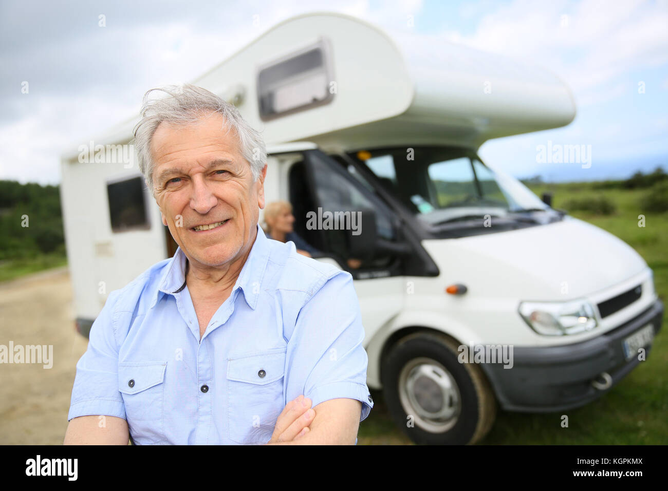 Portrait of happy senior man standing in front of motorhome - Stock Image