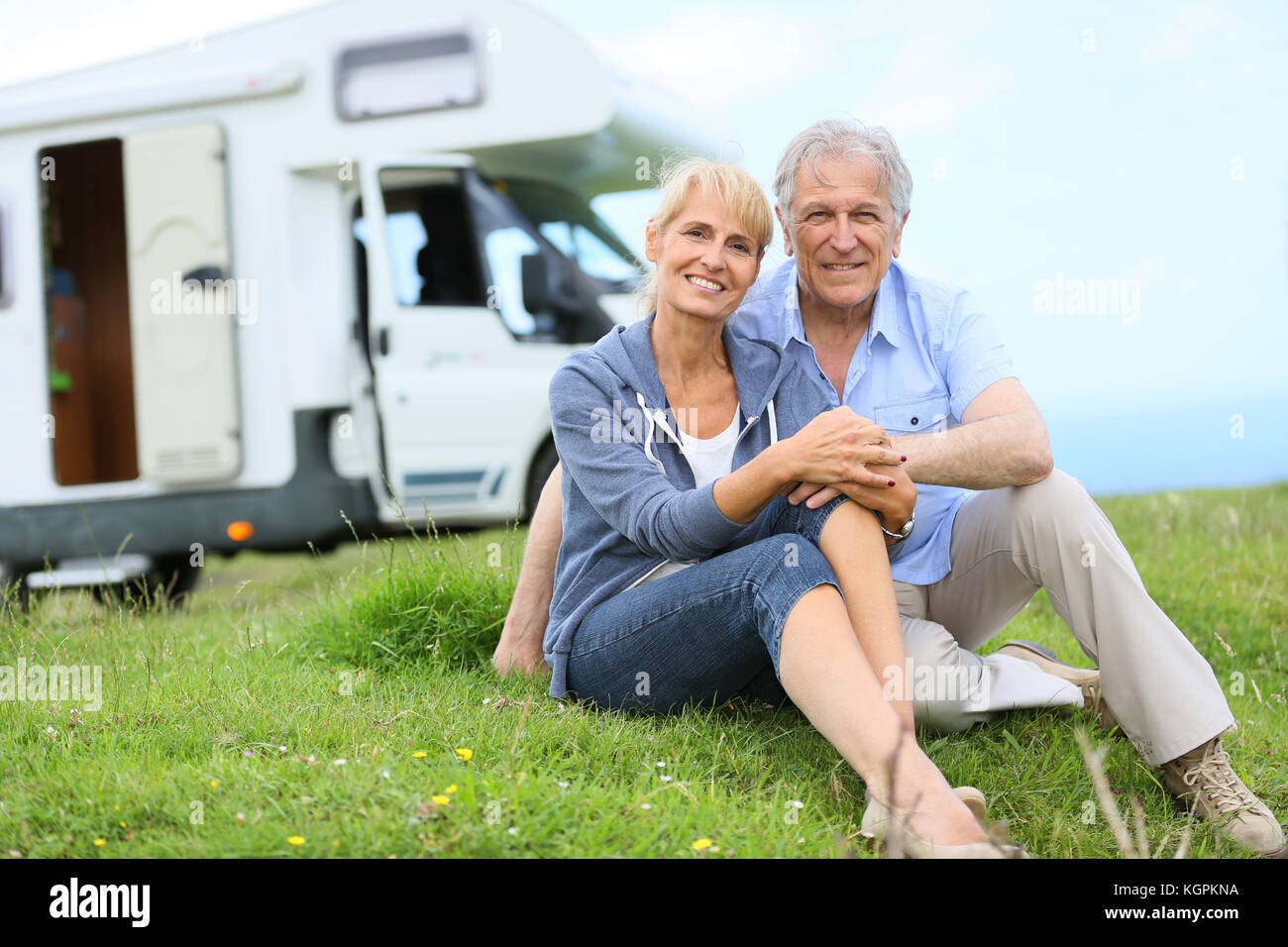 Happy senior couple sitting in grass, camper in background - Stock Image