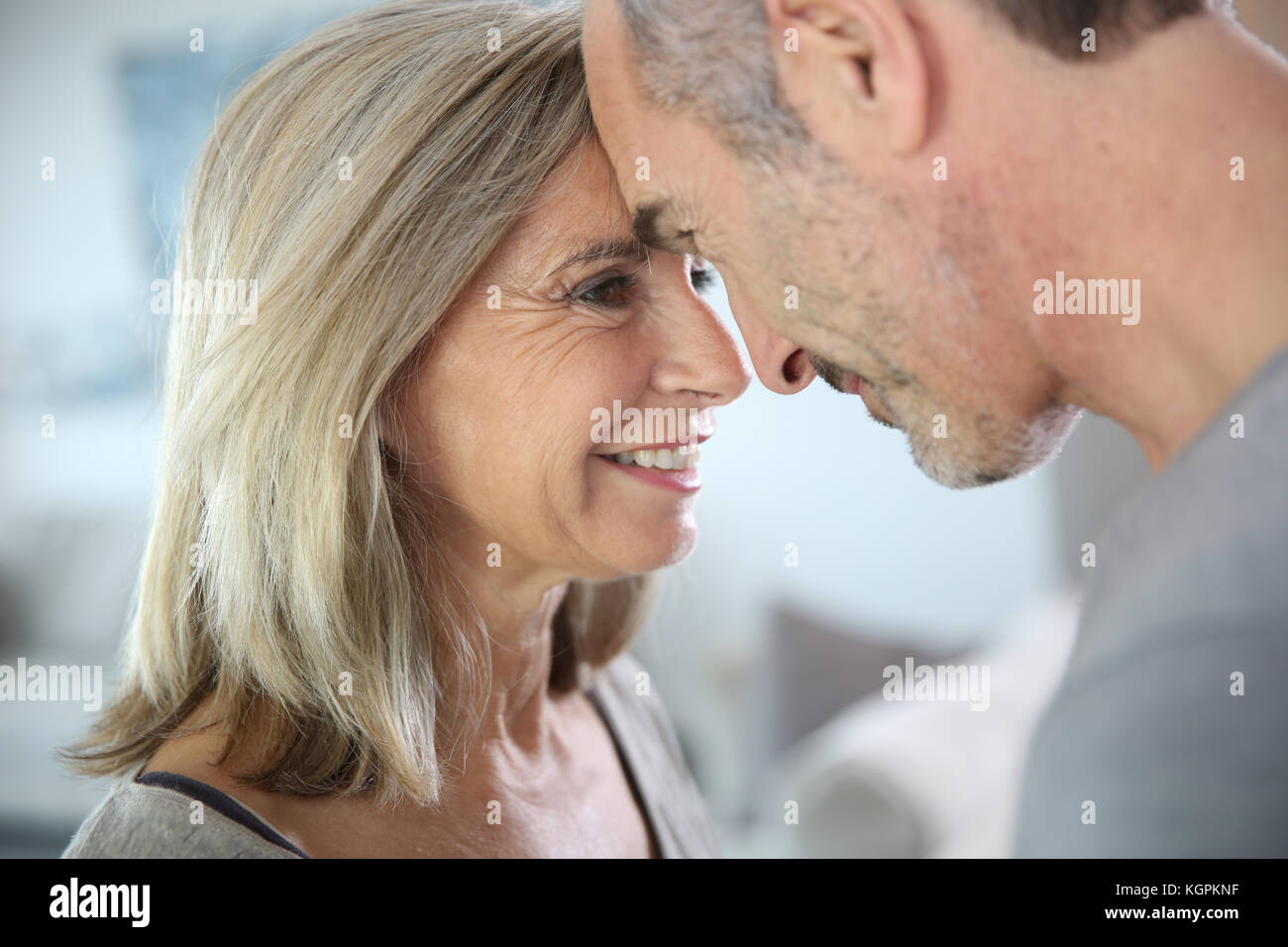 Loving senior couple looking at each other's eyes - Stock Image