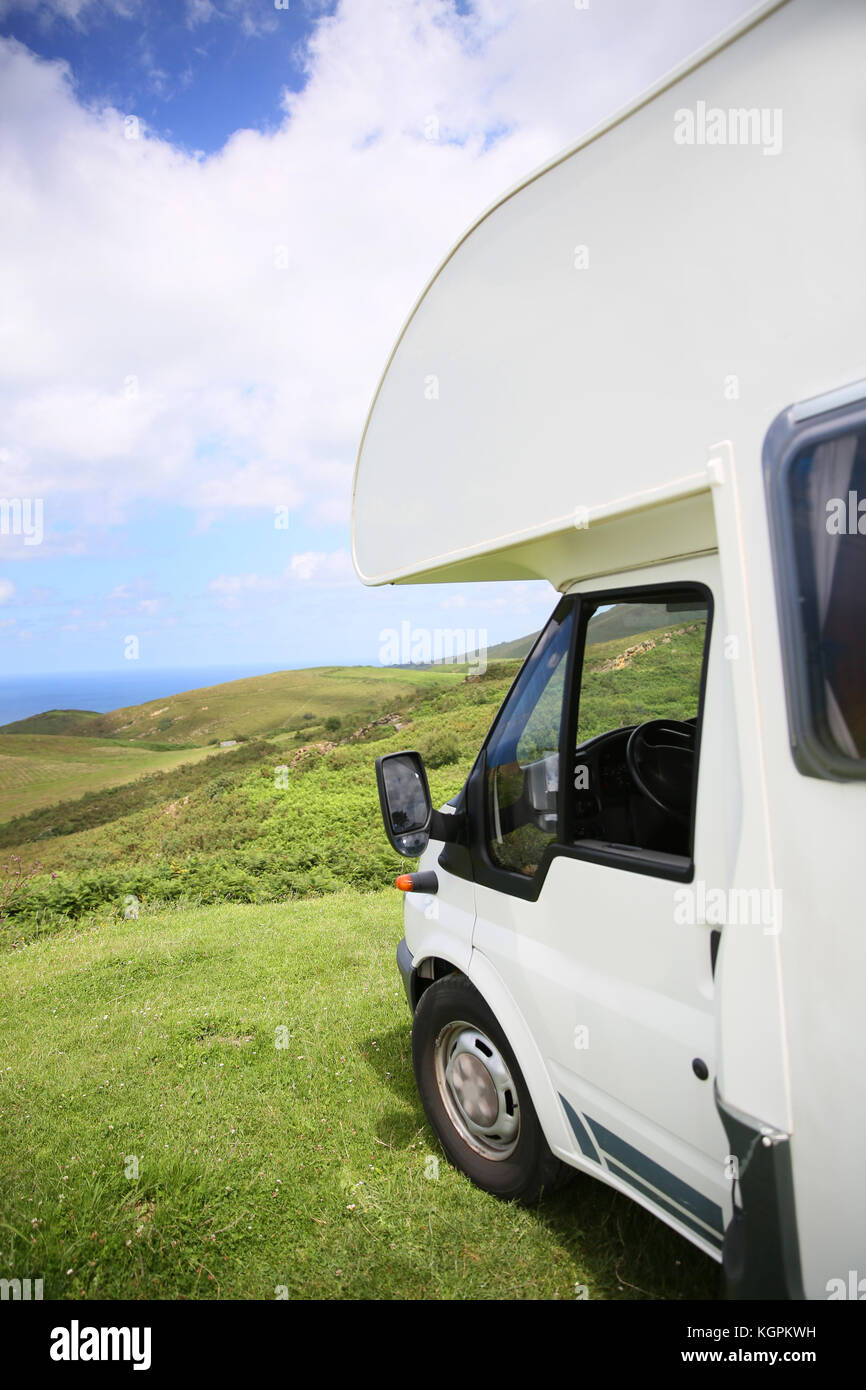 View of camper parked on hill by the sea - Stock Image