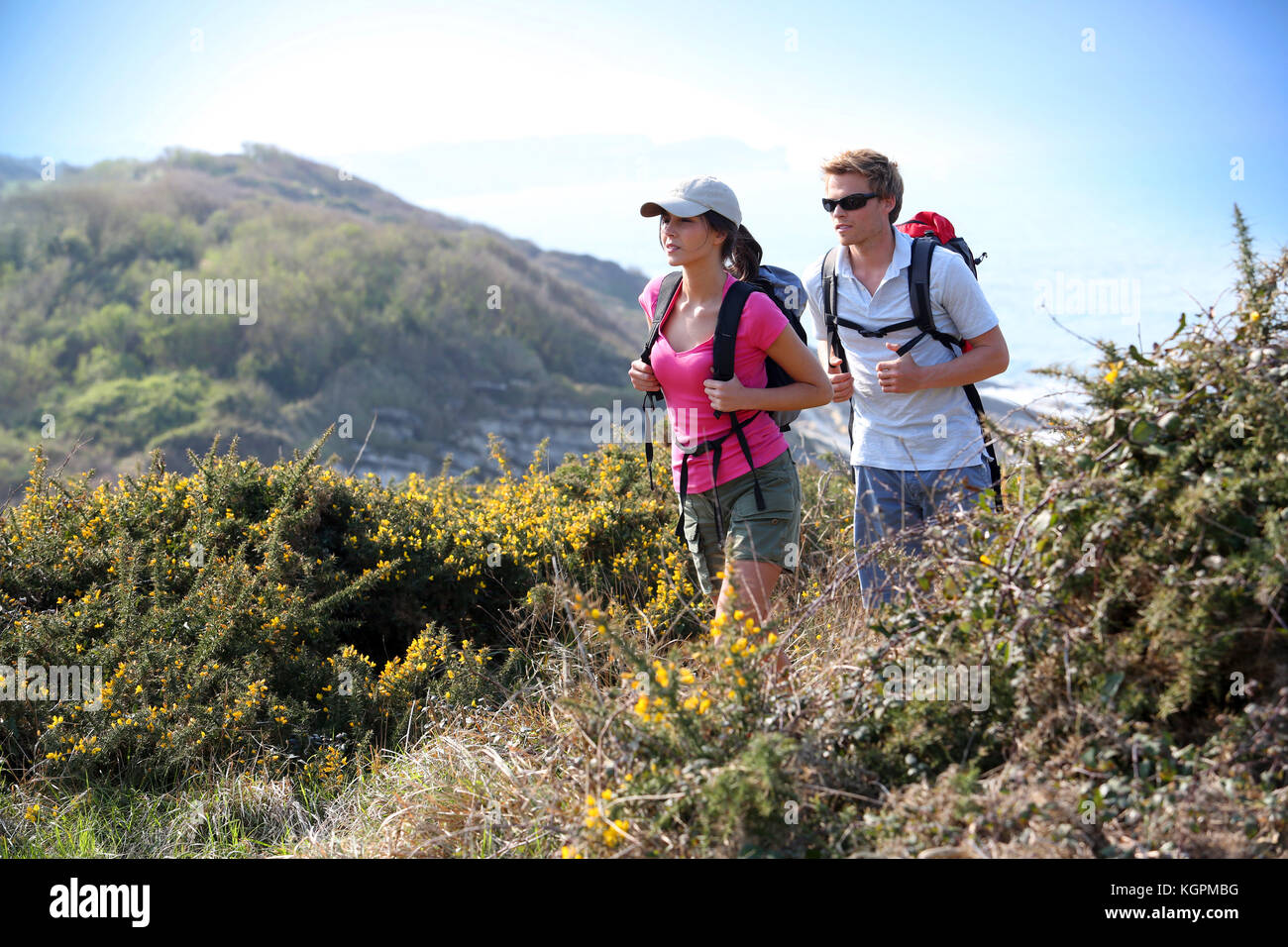 Couple of hikers in country field by the ocean - Stock Image