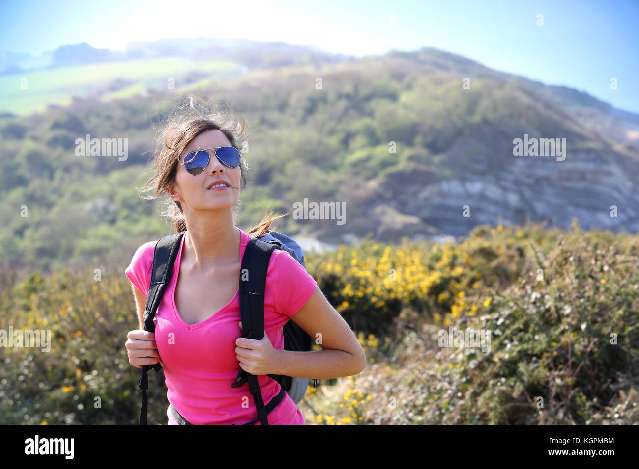 Smiling hiker girl walking in country path - Stock Image
