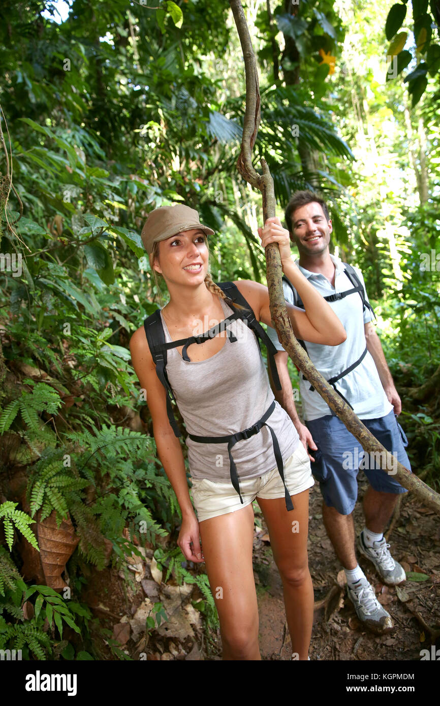 Couple on a trekking day in tropical forest - Stock Image