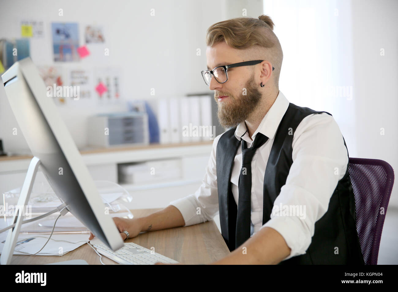 Young man in office working on desktop computer - Stock Image