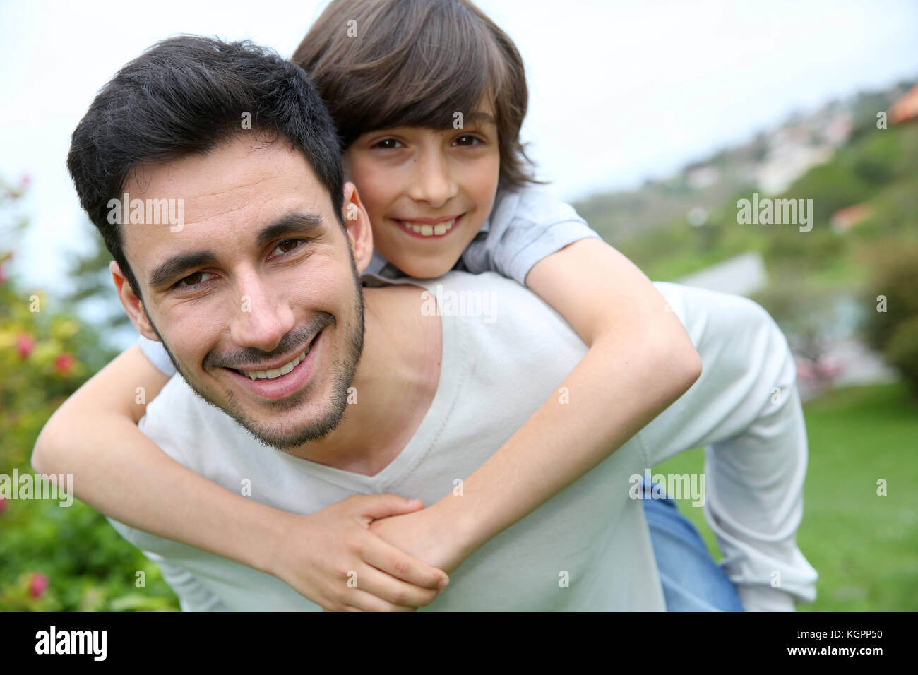 Father giving piggyback ride to his son - Stock Image
