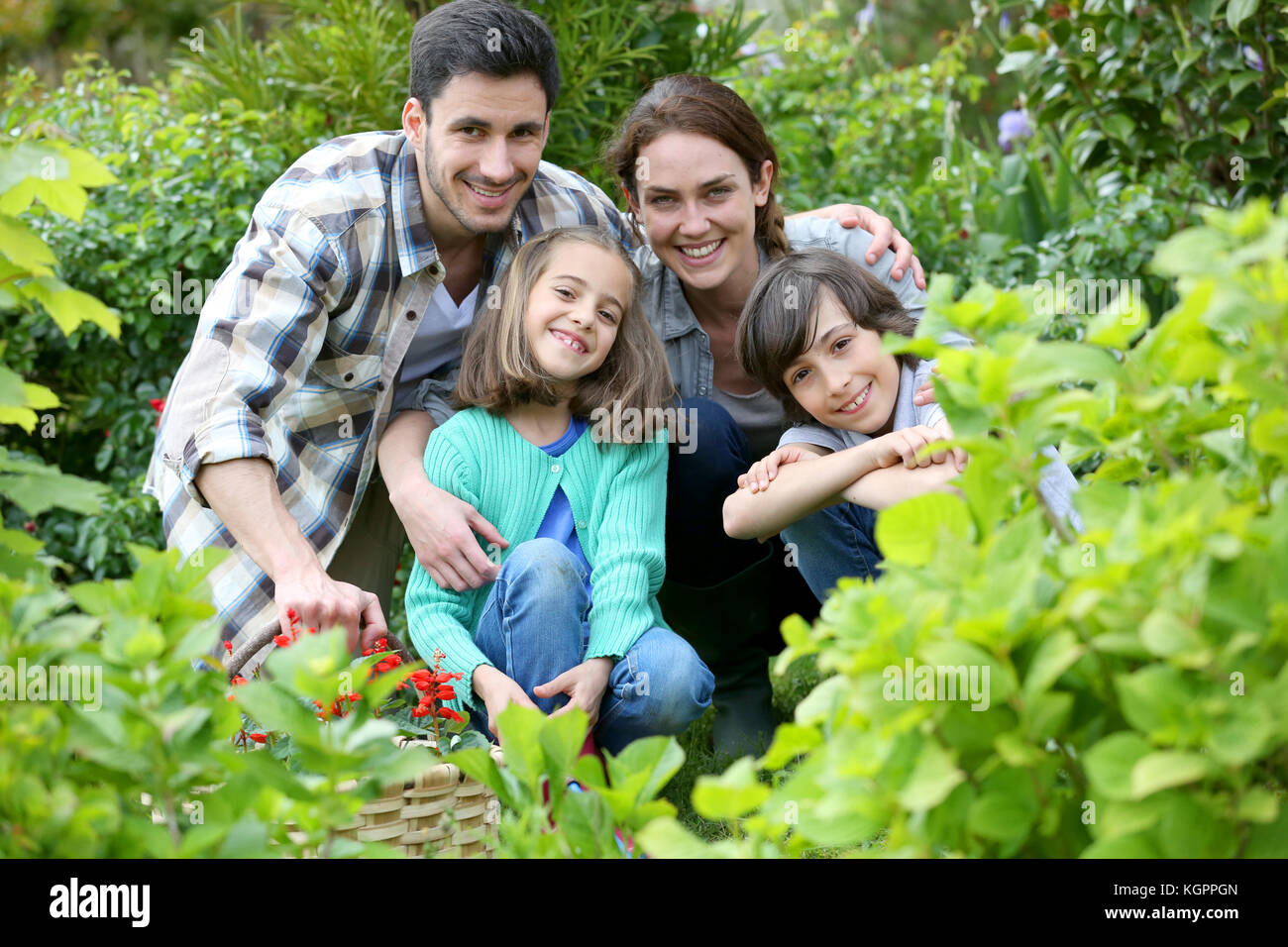 Portrait of happy family gardening together - Stock Image