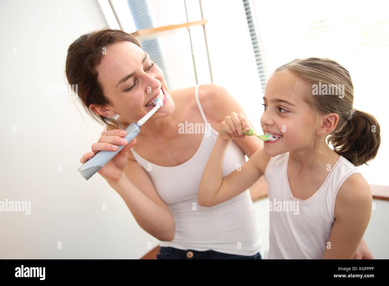 Mother teaching little girl how to brush her teeth - Stock Image