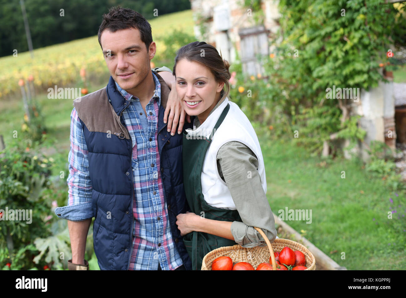 Cheerful couple standing in kitchen garden - Stock Image