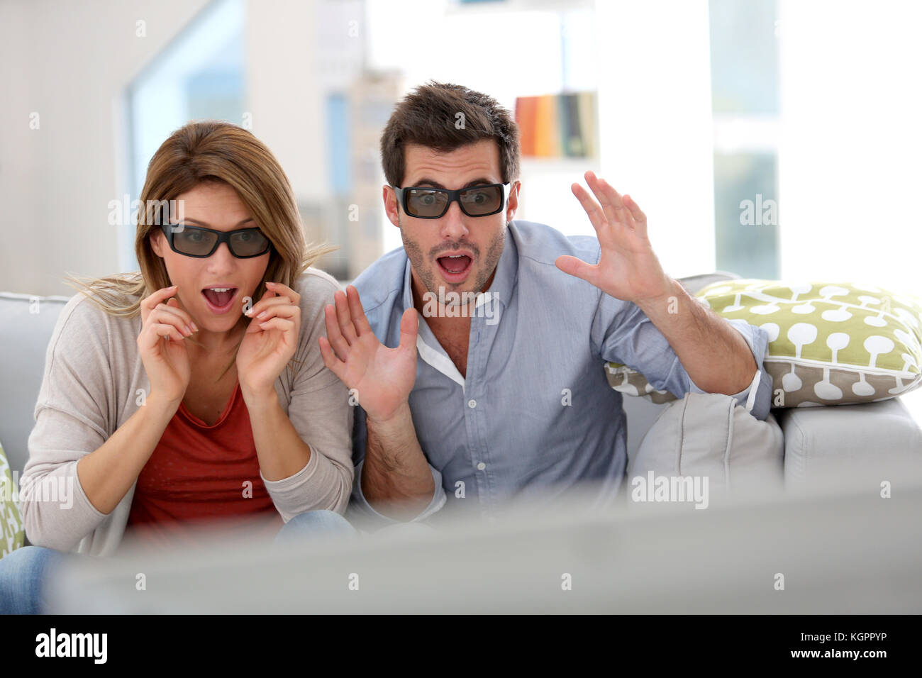 Couple at home watching 3D movie with eyeglasses - Stock Image