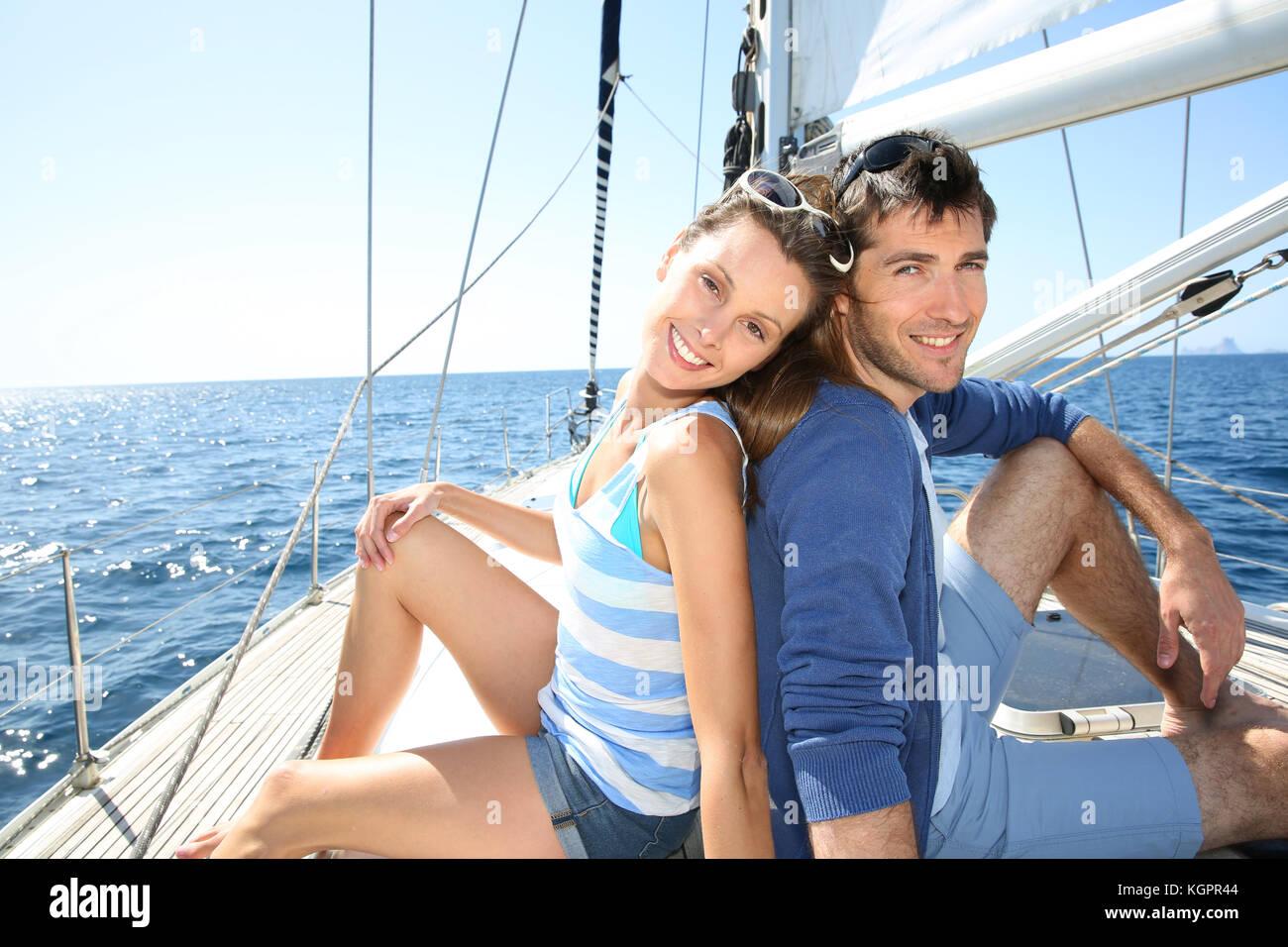 Smiling couple enjoying cruising journey on sailboat - Stock Image