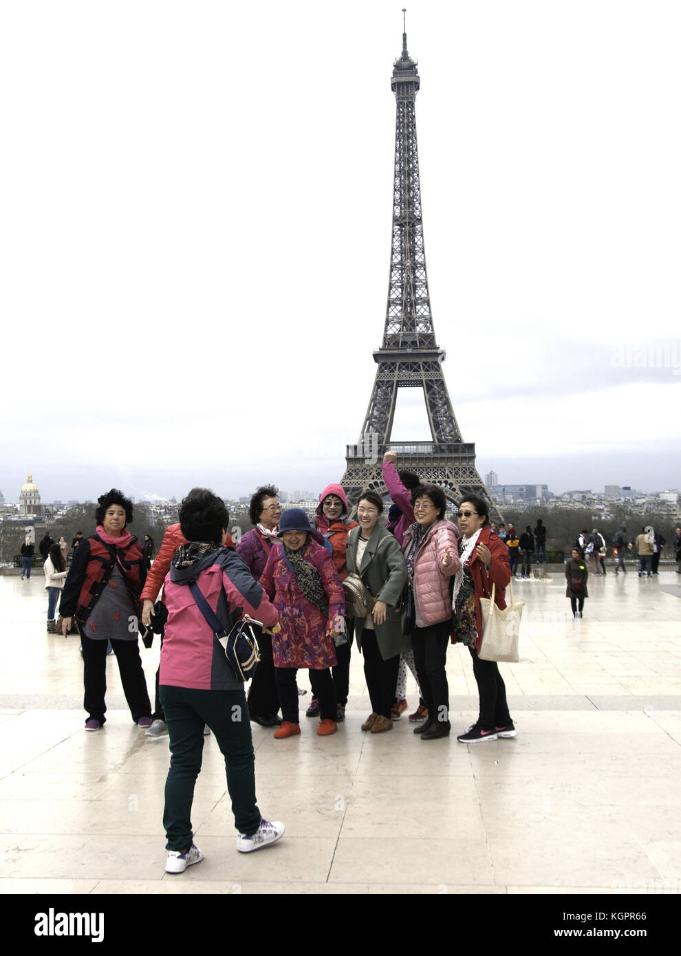 Tourists, all women, gather for the mandatory souvenir photo with Paris's famous Eiffel tower behind them - Stock Image