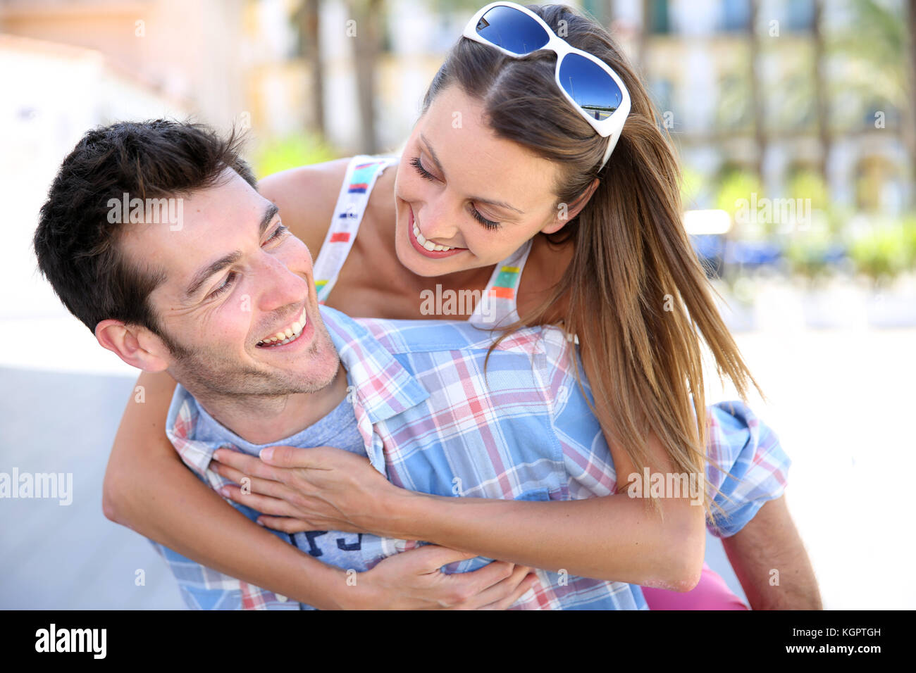 Man giving piggyback ride to girlfriend - Stock Image