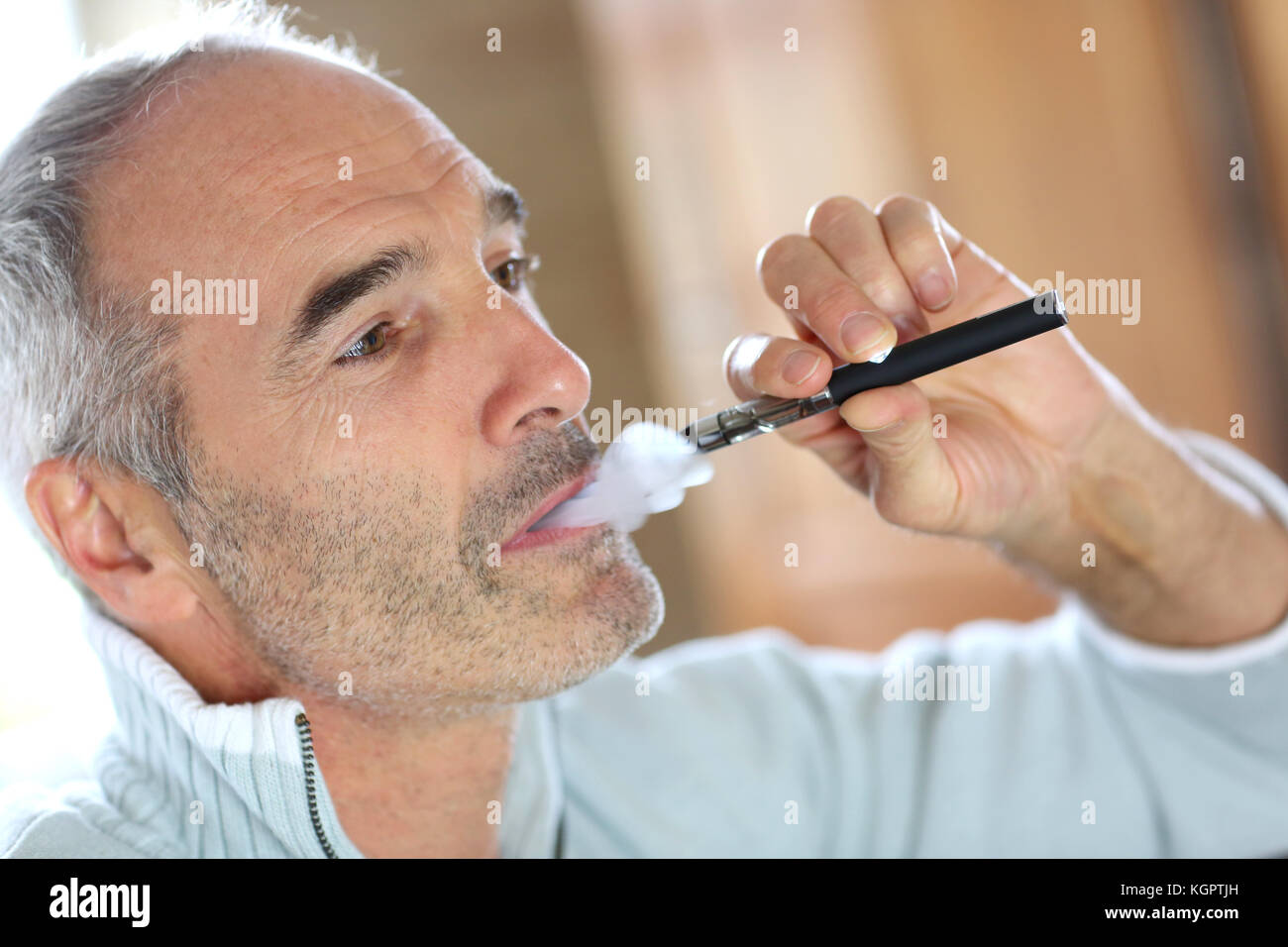 Portrait of senior smoker with electronic cigarette - Stock Image