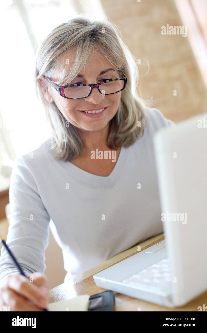 Senior woman at home figuring out income tax - Stock Image