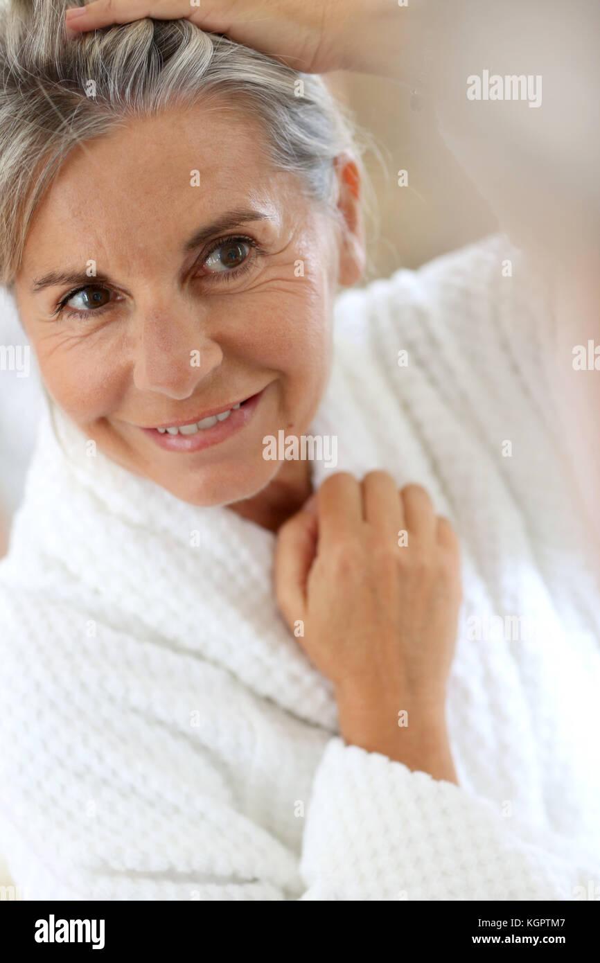 Senior woman worried by hair getting grey - Stock Image