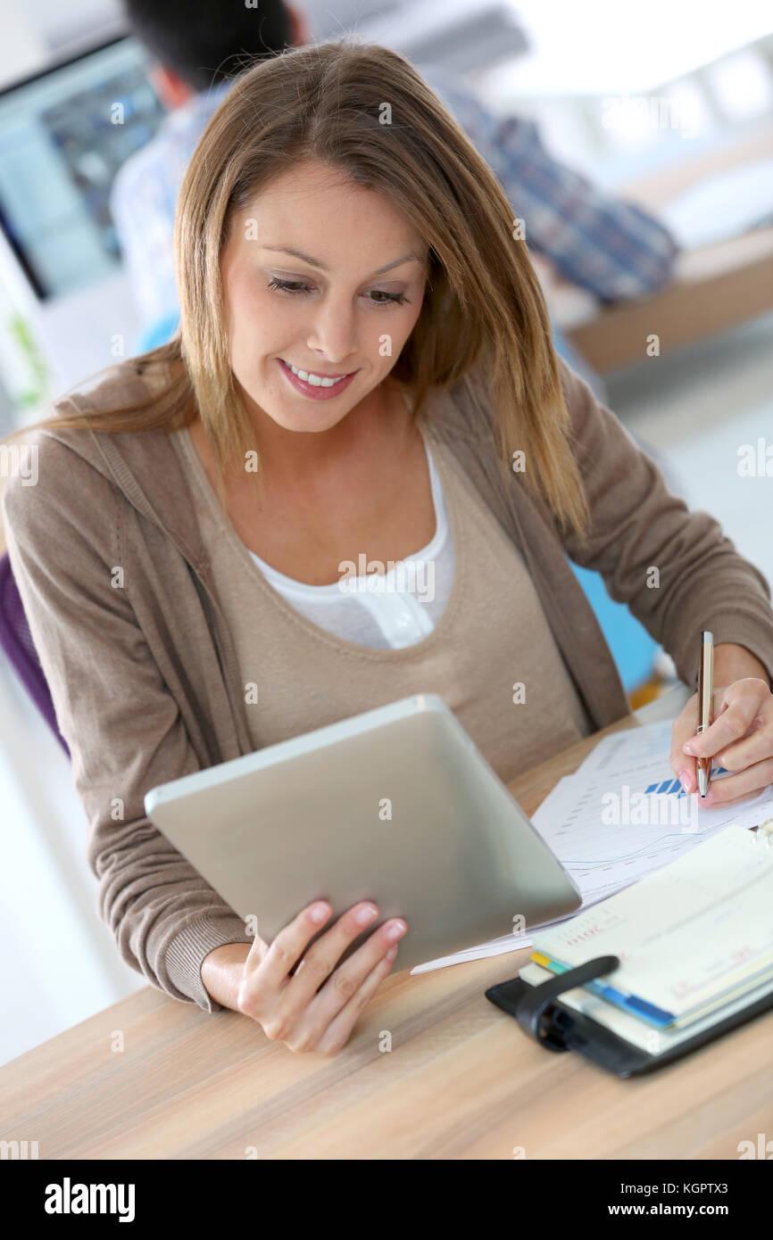 Portrait of smiling office worker using digital tablet - Stock Image