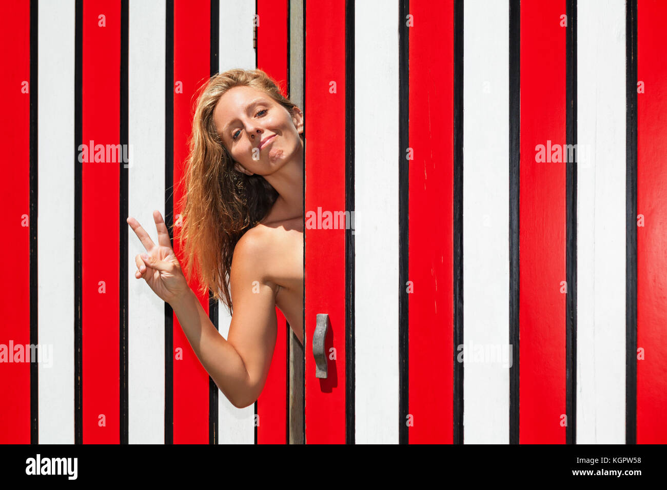 Happy smiling young blond woman against red striped wall of beach changing cabin has fun, raising hand, showing - Stock Image