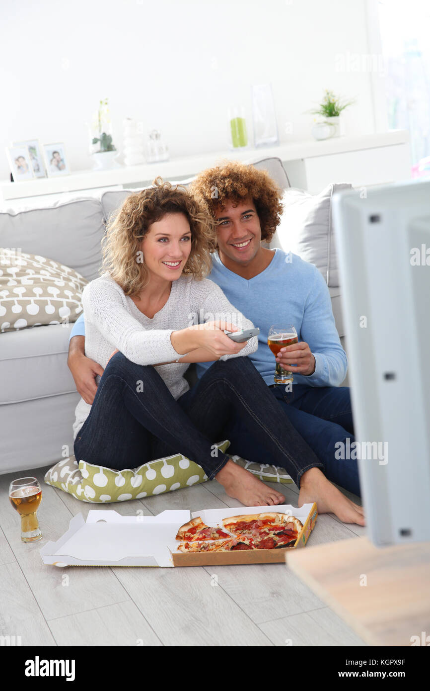Cheerful couple at home having pizza in font of TV - Stock Image