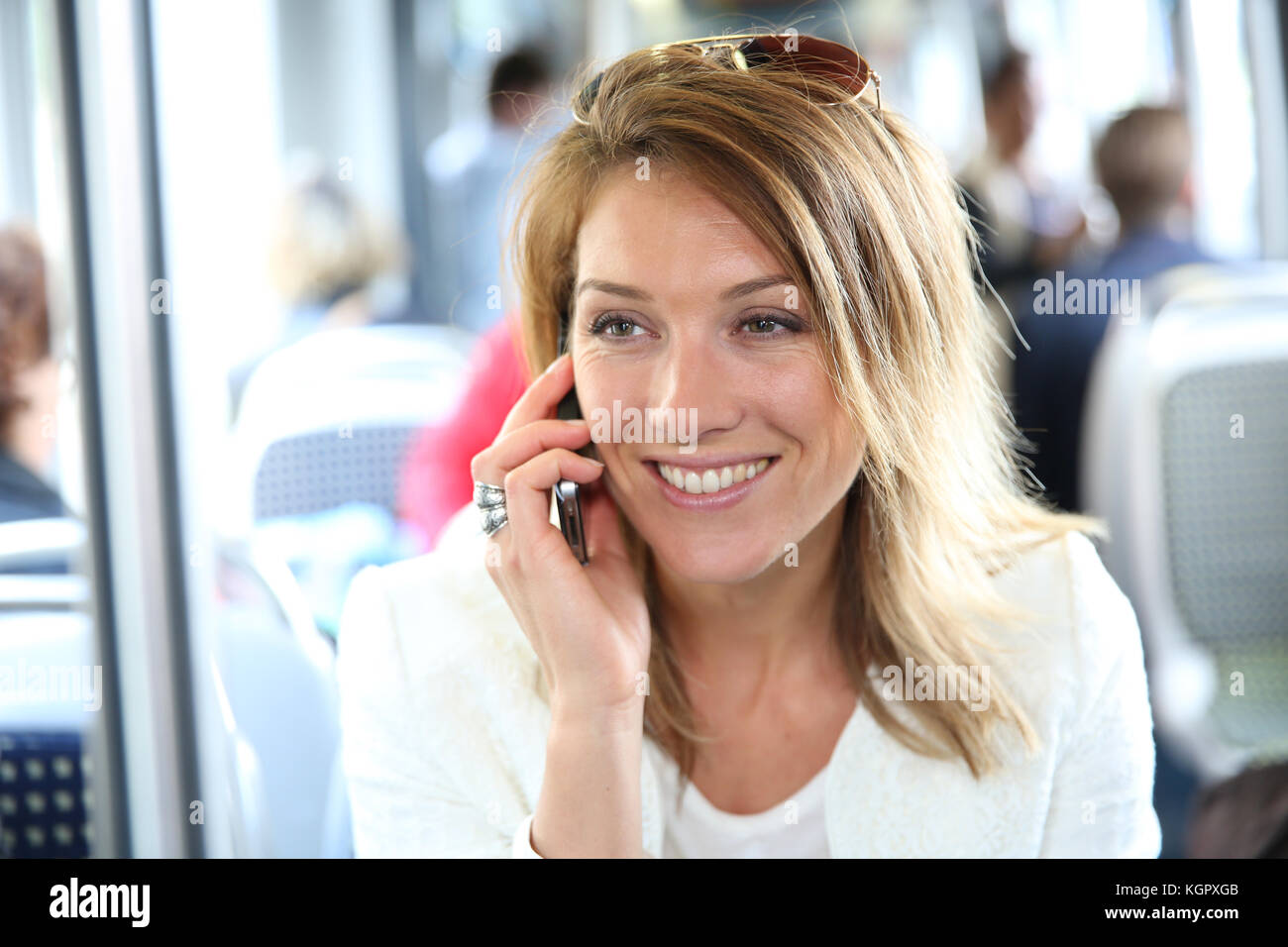 Smiling girl in city train using smartphone - Stock Image
