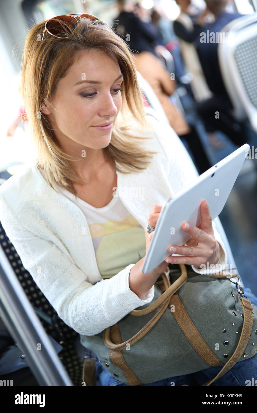 Woman in city train websurfing with tablet - Stock Image