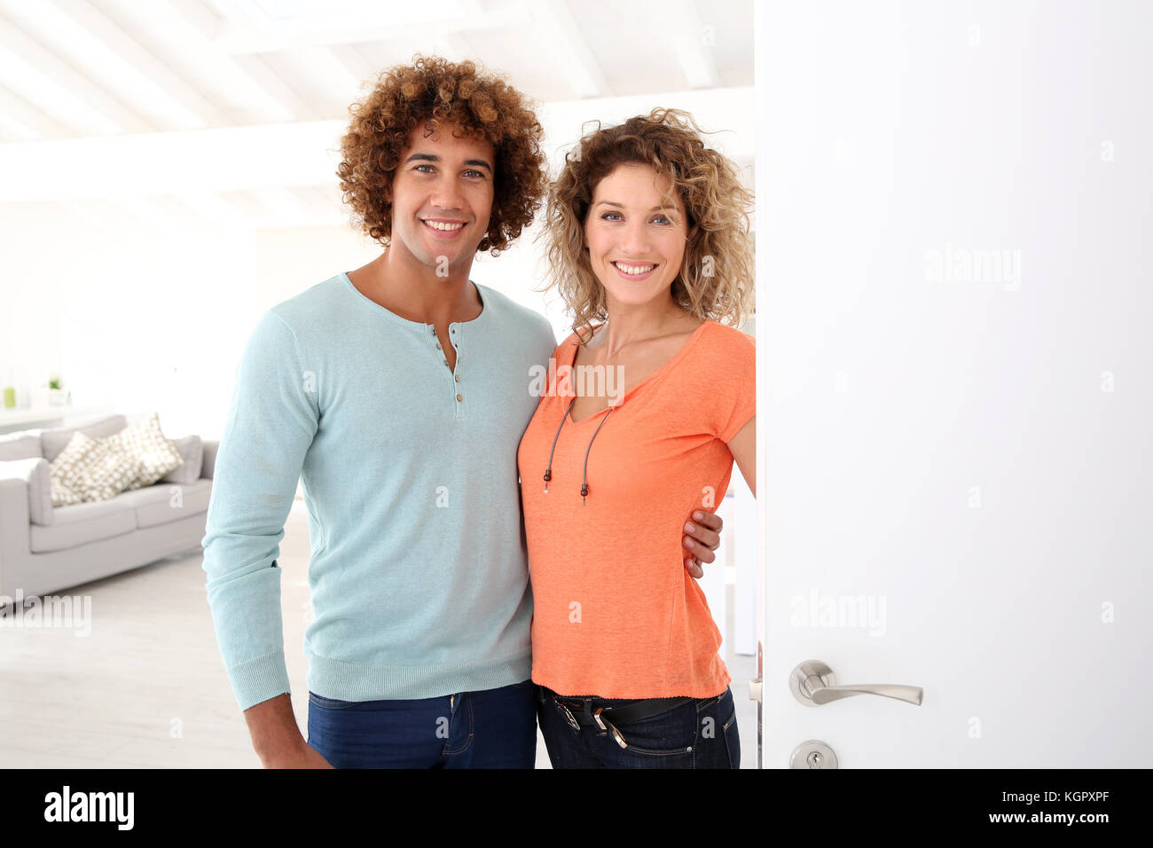 Cheerful couple opening new home entrance door Stock Photo