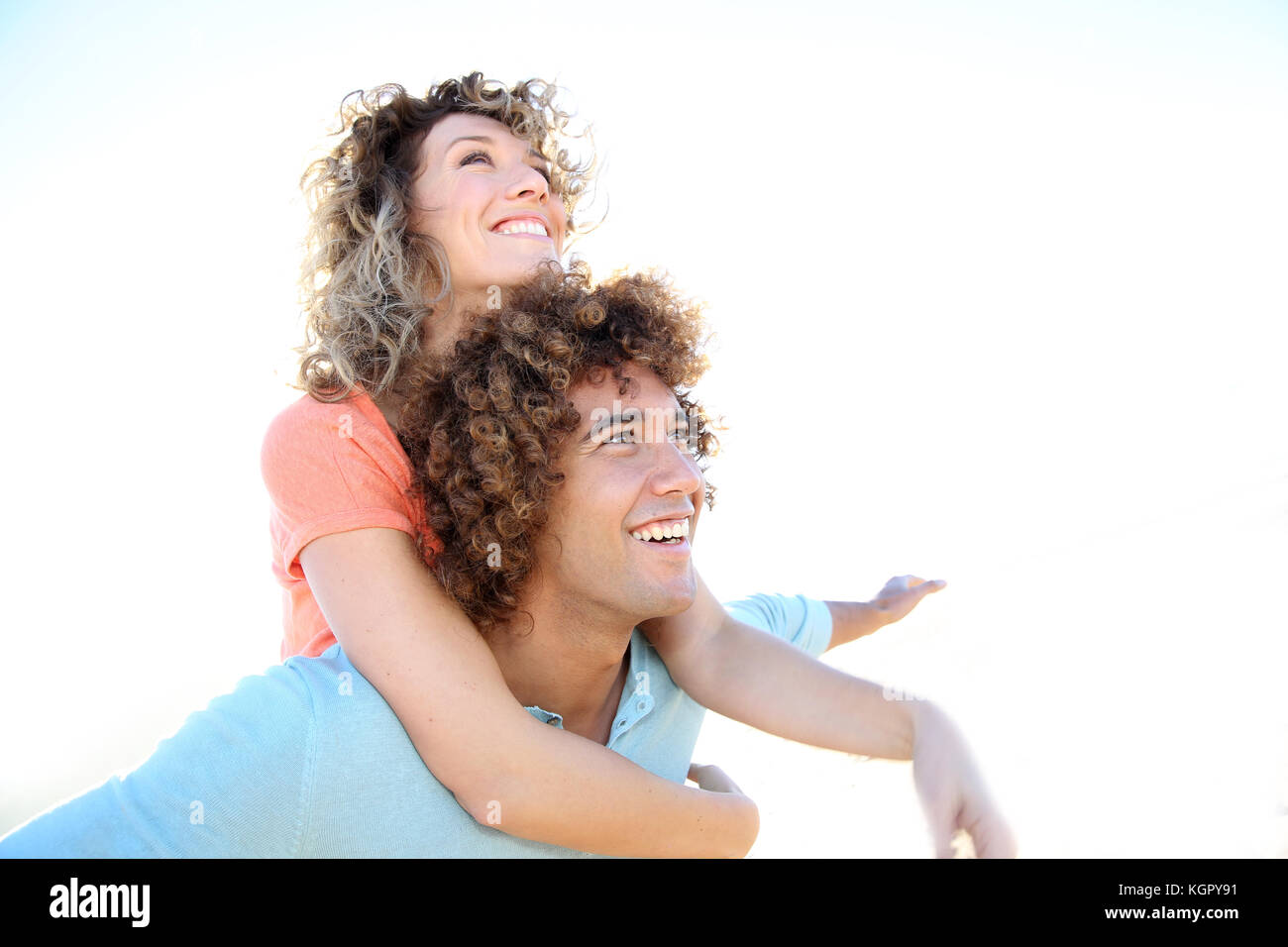 Man giving piggyback ride to girlfriend on the beach - Stock Image